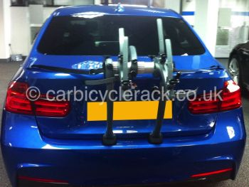 Rear view of a blue bmw 3 series saloon with a bike rack fitted in a bmw showroom