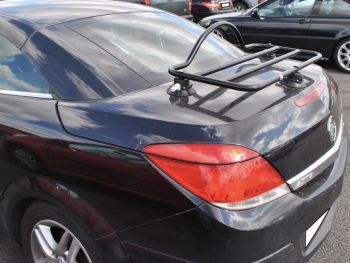 black vauxhall astra convertible with a revo-rack luggage rack fitted to the bot photographed from the side