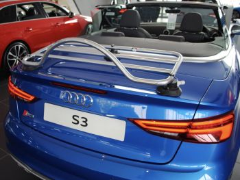 blue Audi a3 s3 convertible with a revo-rack pa luggage rack fitted hood down in an audi dealership photographed from the rear