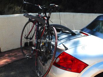 side view of a silver audi tt roadster convertible with a bike rack fitted carrying a bike