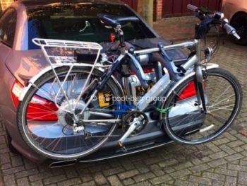 grey mercedes sl with a bike rack fitted carrying a bike outside a garage