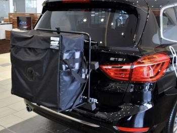 black bmw 218i grand tourer with a hatch-bag roof box alternative fitted