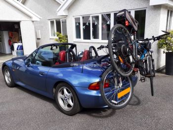 blue bmw z3 convertible hood down outside a house with a bike rack fitted carrying two bikes