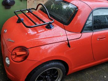 Daihatsu copen in red with a black revo-rack luggage rack fitted on a rainy day