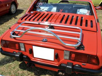 red fiat x1/9 in a field on a very sunny day with a stainless steel luggage rack fitted