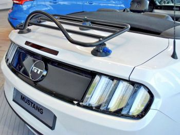 White ford mustang convertible with the hood down and a luggage rack fitted in a ford showroom