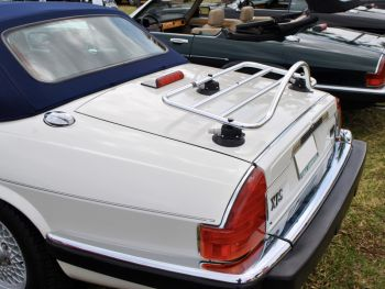 white jaguar xjs convertible with a blue hood at a car show with a stainless steel luggage rack attached to the boot