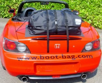red honda s2000 beside a hedge hood down on a sunny day with a boot-bag original boot rack fitted