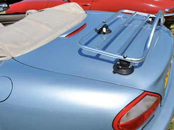 light blue jaguar xk8 convertible with the hood down and a revo-rack stainless steel luggage rack fitted on a sunny day