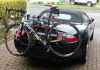 black Jaguar xk convertible with a bike rack fitted carrying a bike