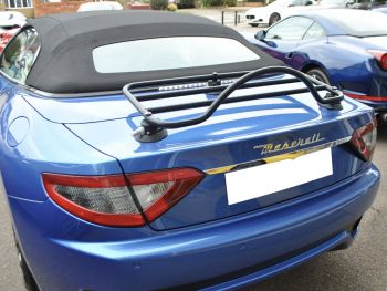 Bright blue maserati convertible with a black luggage rack fitted
