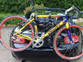 black mazda mx5 mk3 with a bike rack fitted carrying a yellow red and blue racing bike