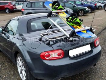 Mazda Miata with a luggage rack fitted with skis and a snowboard on it