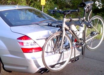 silver mercedes benz s class with a bike rack fitted carrying two bikes.