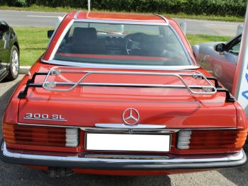 red mercedes sl r107 300 with a hardtop fitted on a sunny day with a stainless steel boot rack fitted