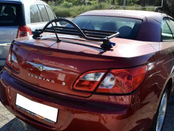 red 2007-2010 chrysler sebring with a revo-rack black luggage rack fitted on a sunny day