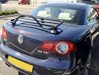 dark blue volkswagen vw eos on a sunny day with the roof up and black luggage rack fitted to the boot / trunk